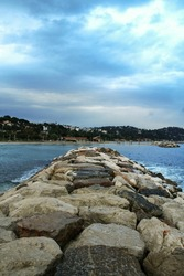 Plage du Mourillon beach, deserted, during a rainy cloudy afternoon, with a rock dike sea wall. Mourillon is one of the main beaches of the city of Toulon, France, on the French riviera.