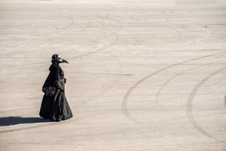 plague doctor alone on a large paved area