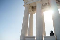 plague doctor stands between columns