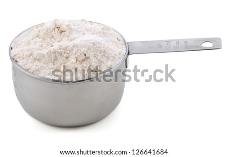 Plain / all purpose flour presented in an American metal cup measure, isolated on a white background