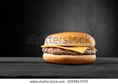 Plain beef burger with cheese on wooden table isolated on black background.