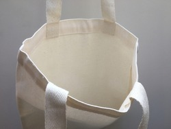 Plain blank canvas bag hanging on wall seeing inside of bag with space for logo, brand name, runaround or wraparound text
