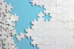 plain blue background with disassemble incomplete white jigsaw puzzle for your background or your content.