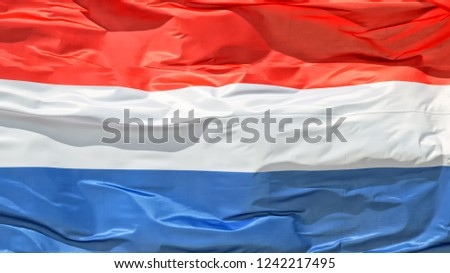Plain crop view of crumpled Netherlands national state sign flag waving by wind natural colors exterior panoramic landscape background view patriotic theme scene #1242217495