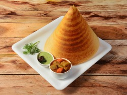 Plain Dosa, a south Indian traditional and popular Breakfast served with chutney and sambar over a rustic wooden background, selective focus