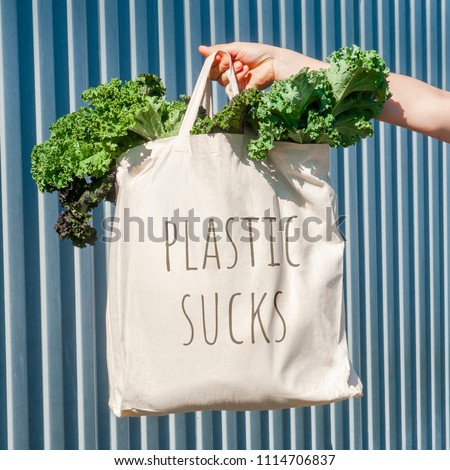 "Plain flex eco-bag with sign ""Plastic sucks"" with green fresh kale and arm on the background of the metal fence or wall"