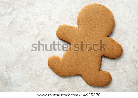 Plain gingerbread man on marble background.  Ideal as simple concept  or with your customized decorations and text added.