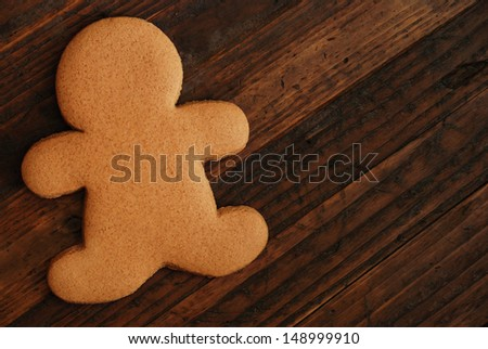 Plain gingerbread man on rustic, dark wood background with copy space.
