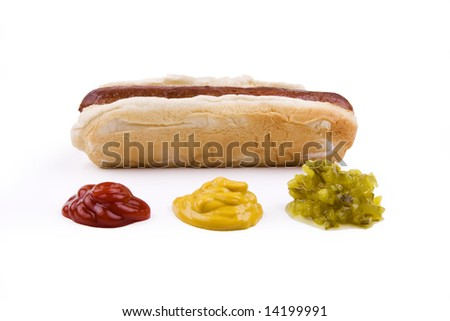 Plain hotdog on a bun with ketchup, mustard, and relish in front.  Isolated on white.