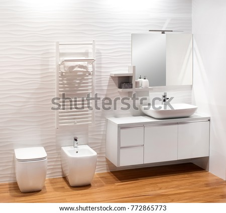 Plain monochromatic white bathroom with simple vanity cabinet, bidet and toilet on a natural wood floor