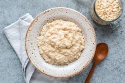 Plain oatmeal porridge in bowl. Healthy vegan vegetarian breakfast food, whole grain porridge oats
