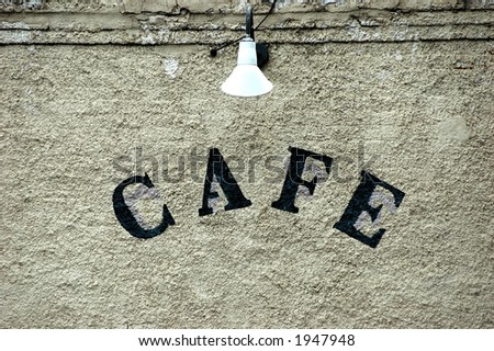 plain off white wall with word cafe in dark letters under lampshade