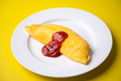 plain omelette with tomato ketchup on yellow background