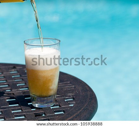 Plain pint glass of beer being poured sitting on table by blue swimming pool