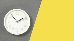 Plain wall clock in the center of grey and yellow background. Ten o'clock. Close up banner with copy space, time management or school concept and lunch time. Opening or closing hours. Schedule