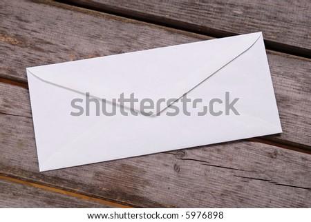 Plain white envelope on a wood picnic table