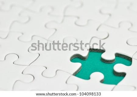 Plain white jigsaw puzzle, on Green background.