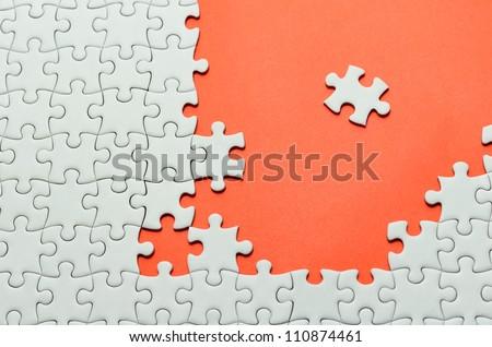 Plain white jigsaw puzzle, on orange background.