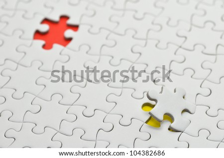 Plain white jigsaw puzzle, on Yellow red background.
