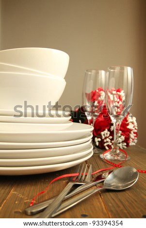 Plain white plates, bowls and glass of wine