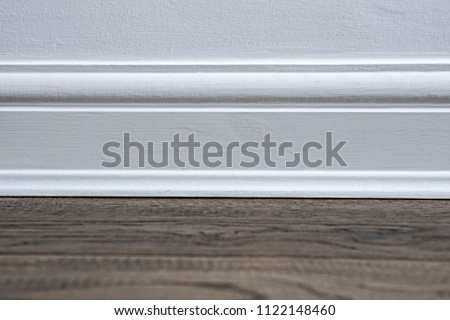 Plain white wooden skirting board against a dark wooden floor. - Shutterstock ID 1122148460