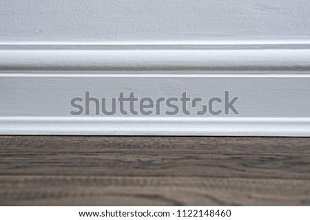 Plain white wooden skirting board against a dark wooden floor. - Shutterstock ID 1122148460