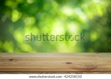 Plain wooden table surface on a blurred outdoor background