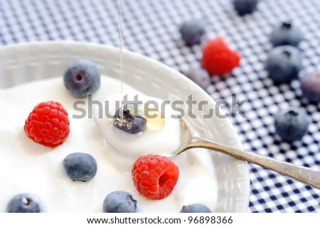 Plain yoghurt topped with blueberry and raspberry