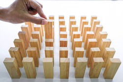 Plan and strategy in business, Risk To Make Business Growth Concept With Wooden Blocks, hand of man has piling up and selecting a wooden block.