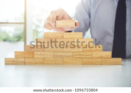 Plan and strategy in business, Risk To Make Business Growth Concept With Wooden Blocks, hand of man has piling up and stacking a wooden block. #1096733804