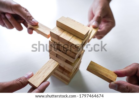 Plan and strategy in business, Risk To Make Business Growth Concept With Wooden Blocks, hand of man has piling up and stacking a wooden block. Stock photo ©