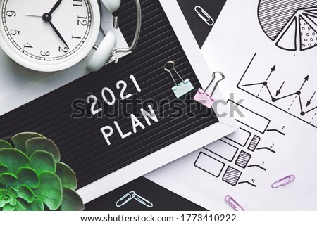 plan for 2021. Alarm clock and office accessories on the table top view.