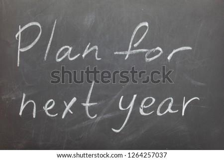 Plan for next year drawn on chalkboard. Phrase