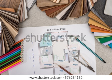 plan house with wooden models, pencils, pen on the table. - Shutterstock ID 576284182