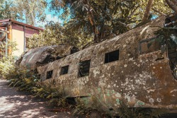 Plane crash in Australian jungle. Old rusty abandoned airplane wreckage. Vintage brown aeroplane wreck. Travel, transportation, disaster, aviation, accident concepts. Rescue abandoned in bushes.