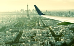 Plane flies above Paris, France. Aerial panoramic view of Eiffel tower from airplane window. The plane's wing over streets of Paris. Concept of air travel to Paris. Flight in Europe in summer.