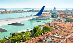 Plane flies above Venice, Italy. Aerial panoramic view of city and sea from airplane window. The plane's wing over Venice during taking off or landing. Concept of flight, vacation and summer travel.