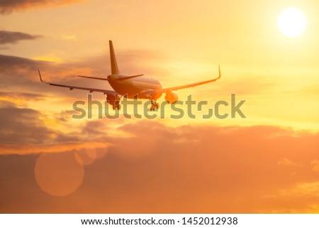 plane flies in sky towards sun.