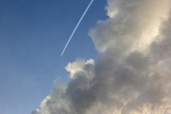 Plane flying from top to bottom with an inversion trail from a large cloud against a blue sky background. Condensation trail from an airplane flying at high altitude. Aircraft with white stripes.