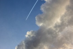 Plane flying from top to bottom with an inversion trail from a white cloud against a blue sky background. Condensation trail from an airplane flying at high altitude. Aircraft with white stripes