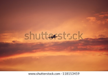 Plane flying upon red and pink sky in the evening