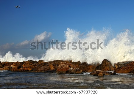 Plane in the sky and waves breaking on a stony beach of Tel-Aviv (Israel)