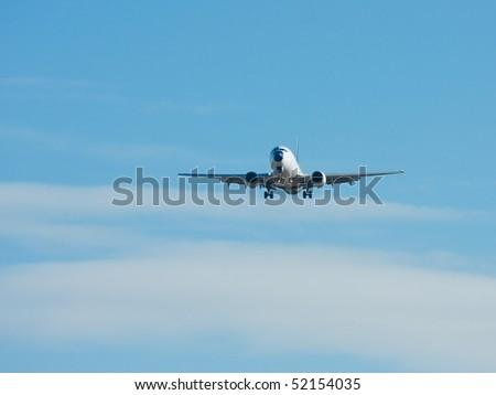 Plane landing against blue sky