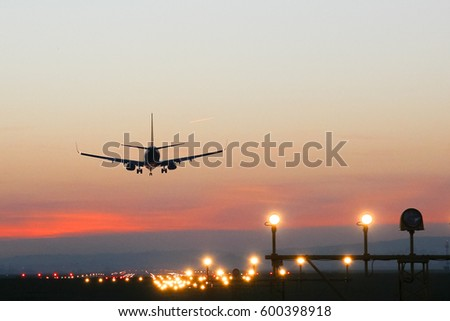 Plane landing at an airfield on the background of sunset - Shutterstock ID 600398918