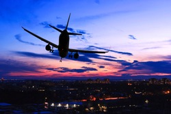 Plane landing in a night city. Steep turn of a jet airplane over the town at sunset. Silhouette of aircraft. Back view. Danger of fall and emergency landing of a passenger airliner