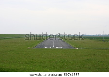 plane landing on runway of a small airfield