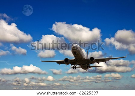 plane landing with blue sky, clouds and the moon