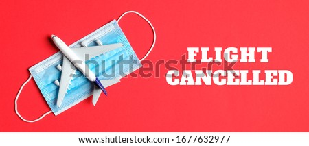 Photo of  Plane model and face mask on a red background with text flight cancelled. Flight cancellation due to the impact of coronavirus (COVID-19) concept.