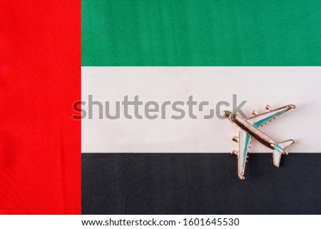 Plane over the flag of the United Arab Emirates United Arab Emirates travel concept. Toy plane on a flag in the background.