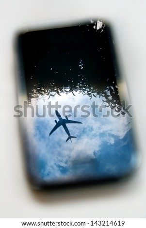plane reflection on mobile phone with blue sky and tree